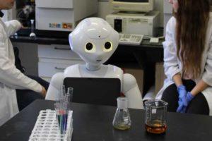 Humanoid robot az egyetemi laborban, kémcsövekkel körülvéve.